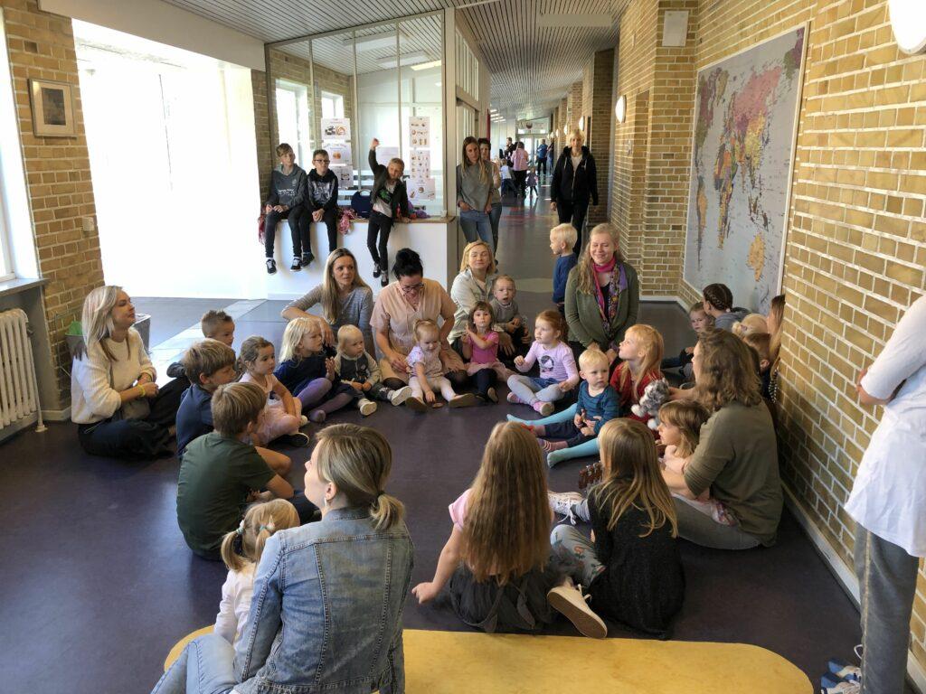 Bērni ar skolotājām sēž aplī uz grīdas